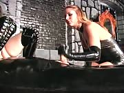 Two girls tag team a dude wrapped up in latex.