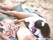 Woman gives her man a handjob while laying on the beach.